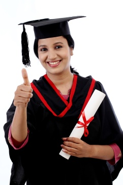 Smiling young graduation student making thumbsup gesture