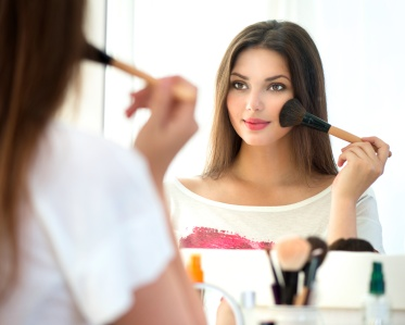 Beautiful girl looking in the mirror and applying makeup