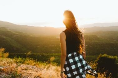 Beautiful young woman enjoying nature at mountain peak.